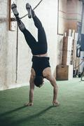 Rear view of sportsman doing handstand in gym Stock Photos