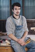 Portrait of young worker sitting with hand tools on bench Stock Photos