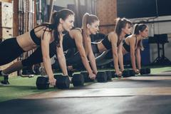 Determined athletes doing push-ups on dumbbells at health club Stock Photos