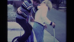 1977: people outside on road trying to tackle riding a one wheeled object  Stock Footage