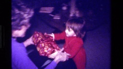 1979: small girl handing over a gift to a middle-aged woman and helping  Stock Footage