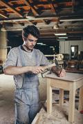 Carpenter hammering nail into wooden stool at workshop Stock Photos