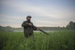 Hunter holding rifle while standing on field against sky Stock Photos