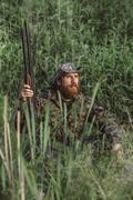 Hunter holding rifle while sitting on grassy field Stock Photos