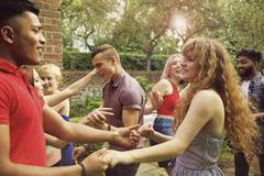 Cheerful friends dancing at yard during party Stock Photos