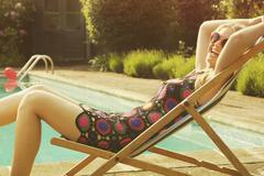 Side view portrait of cheerful woman relaxing on deck chair at poolside Stock Photos