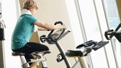 Teenager working out on the exercise bike at the gym Stock Footage