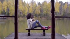 Beautiful girl sitting on the bench and drinking hot tea at the lake Stock Footage