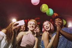 Low angle portrait of happy woman taking selfie with friends at yard Stock Photos
