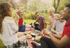 Cheerful friends having food during party at yard Stock Photos
