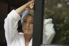 Thoughtful woman in bathrobe leaning at doorway Stock Photos
