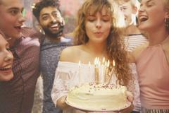 Woman blowing candles while celebrating birthday with friends Stock Photos