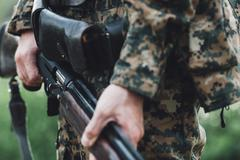 Midsection of hunter holding rifle Stock Photos