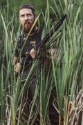 Hunter looking away while standing on grassy field Stock Photos