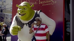 Indian man and wife posing with Shrek statue on Hollywood Boulevard in LA Stock Footage