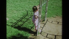1979: a toddler climbing the rails to get to the monkey bars CALIFORNIA Stock Footage