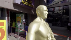 Lifesize Oscar award statues on Hollywood Boulevard in Los Angeles California Stock Footage