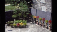 1984: a crowd of asians pass through the stone gate of a potted plant garden Stock Footage