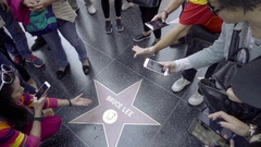 Asian tourists taking pictures of Bruce Lee star on Hollywood Walk of Fame LA Stock Footage