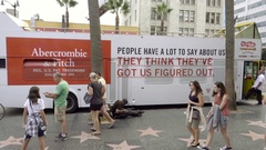 Tour bus with message on it and people walking Walk of Fame stars zooming in LA Stock Footage