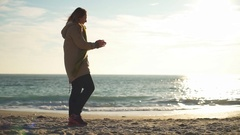A playful beagle plays fetch and brings back a ball to a woman on the beach Stock Footage