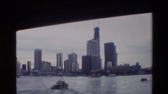 1984: a boat pushing through the water set against a large skyline SINGAPORE Stock Footage