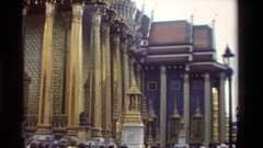 1984: a stone buddha statue rests in front of a decorated building THAILAND Stock Footage