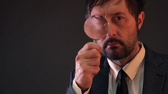 Enlarged eye of tax inspector looking through magnifying glass Stock Footage