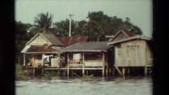 1984: crumbling older houses sit on stilts in the floodplains THAILAND Stock Footage