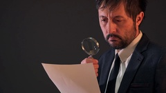 Tax inspector investigating financial documents through magnifying glass Stock Footage
