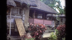 1984: community has airy buildings, grass roofs, stone pillars, flared caps  Stock Footage