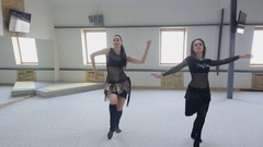 Two beautiful brunettes perform a belly dance in a dancing room Stock Footage