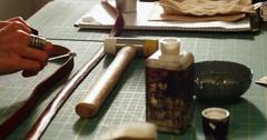 Craftswoman preparing leather belt Stock Footage