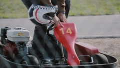 Go-kart track. Man is getting in a kart, shows a thumb up, prepares to put on Stock Footage