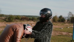 Woman in a crash helmet helping the man take off his helmet.  Stock Footage