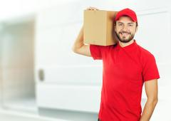 Happy delivery man with box on shoulder in front of a truck Stock Photos