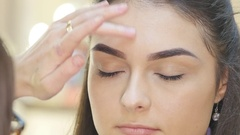 Make-up artist applying powder with a brush on model's cheeks Stock Footage