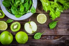 Green vegetables: kiwi, spinach, apple, lime, celery on a rustic wooden bac.. Stock Photos