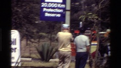 1983: a number of vehicles are placed in a large open area with people around Stock Footage