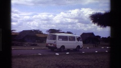 1983: a white van driving down a dirt road past some cabins Stock Footage