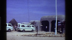 1983: a group of white vans parked along a community of huts KENYA Stock Footage