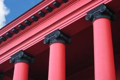 Red columns on the facade in the old architectural building Stock Photos