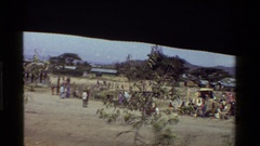 1983: a crowd of people mill about in a field of dry grass KENYA Stock Footage