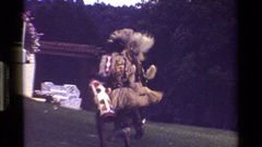 1983: many people wearing costumes while dancing around in a grassy area KENYA Stock Footage