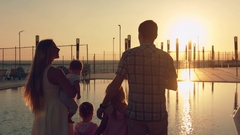 Happy family with three children admiring the sunset reflected in the surface of Stock Footage