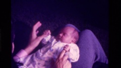 1975: a person sits playing with a small baby laying in it's lap CALIFORNIA Stock Footage