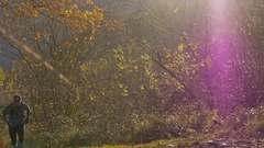 A trail runner runs up a trail with autumn colors, slow motion. Stock Footage