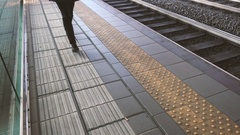 Woman walking near the rails at the train station Stock Footage