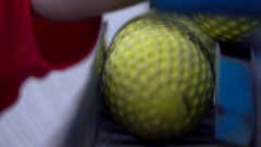 Details of a vintage pitching machine being loaded with yellow baseball balls. Stock Footage