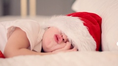 Kid sleeping with santa hat and waiting Santa's gift. Peaceful child Stock Footage